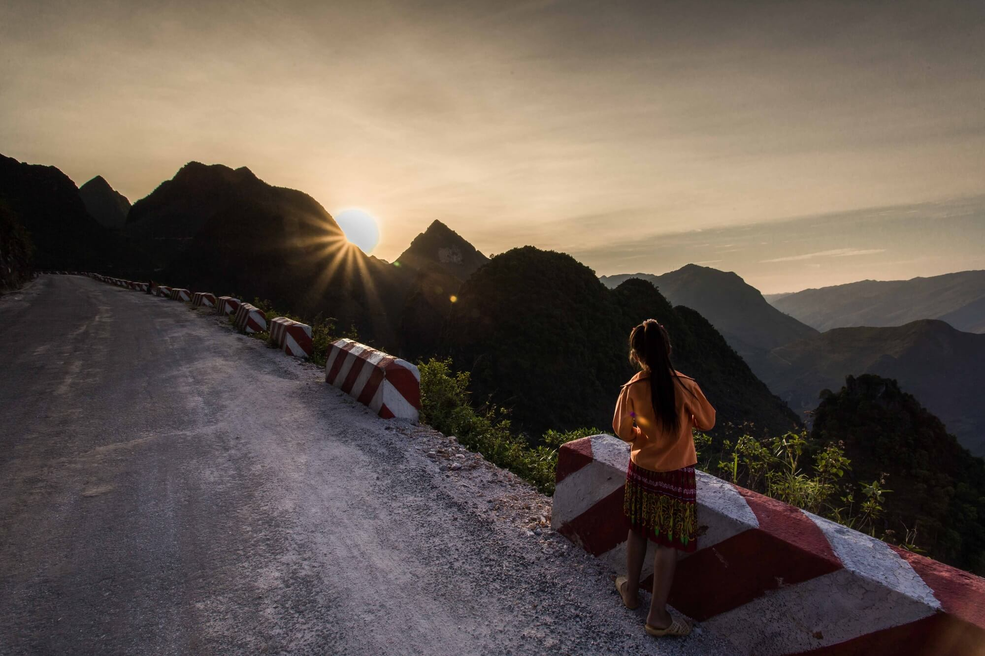 Vietnam minority girl on mountain passage watching the setting sun
