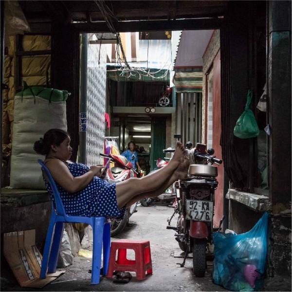 Saigon street seller relaxing in alley